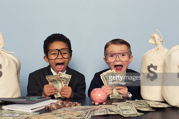 young business children make faces holding lots of money - opwinding stockfoto's en -beelden