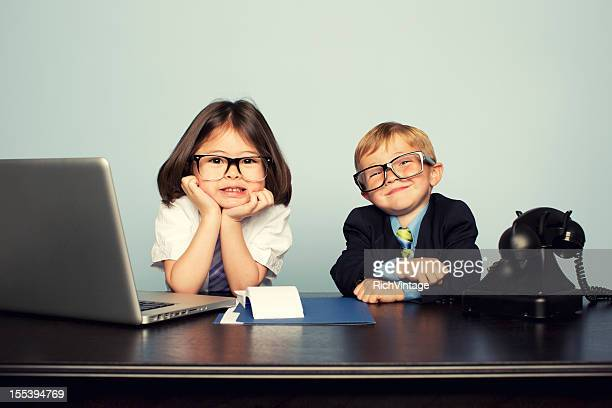 young business children sitting at desk with laptop - talent stockfoto's en -beelden