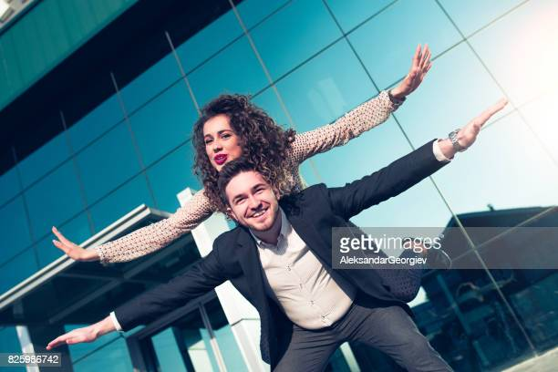young business colleagues celebrating with spread hands and piggyback ride after successfully done job - spreading stock pictures, royalty-free photos & images