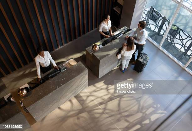 young business couple checking in at hotel and beautiful receptionist helping them - hotel lobby stock pictures, royalty-free photos & images