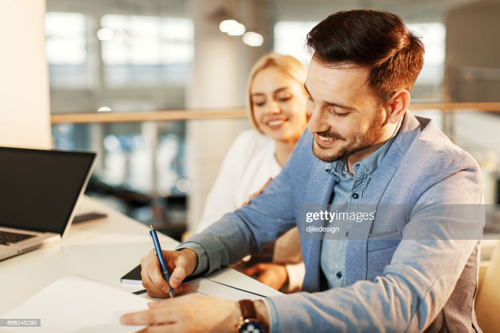Young business couple signing a contract : Stock Photo