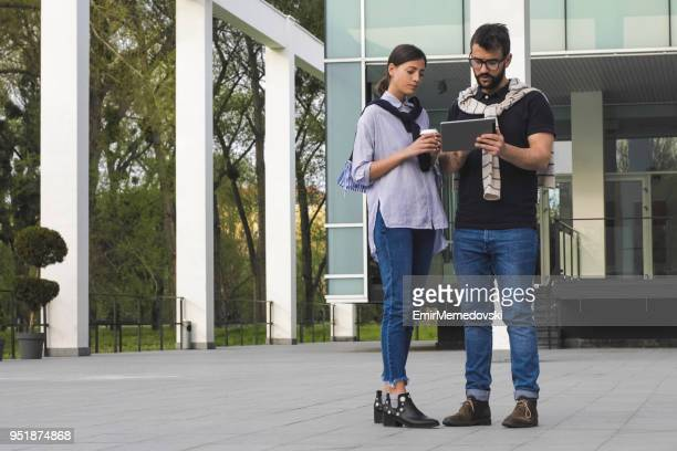 Young business couple using digital tablet outdoors