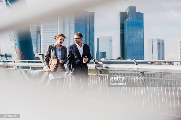 young business couple walking on bridge, talking - wolkenkratzer stock-fotos und bilder