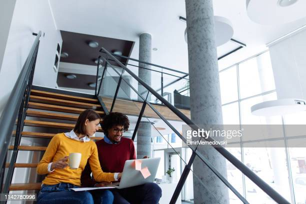 Young business couple with laptop working on the staircase