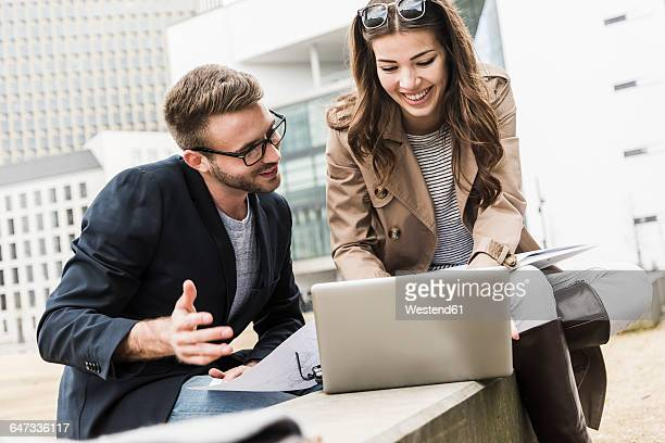 Young business couple working together outdoor, using laptop