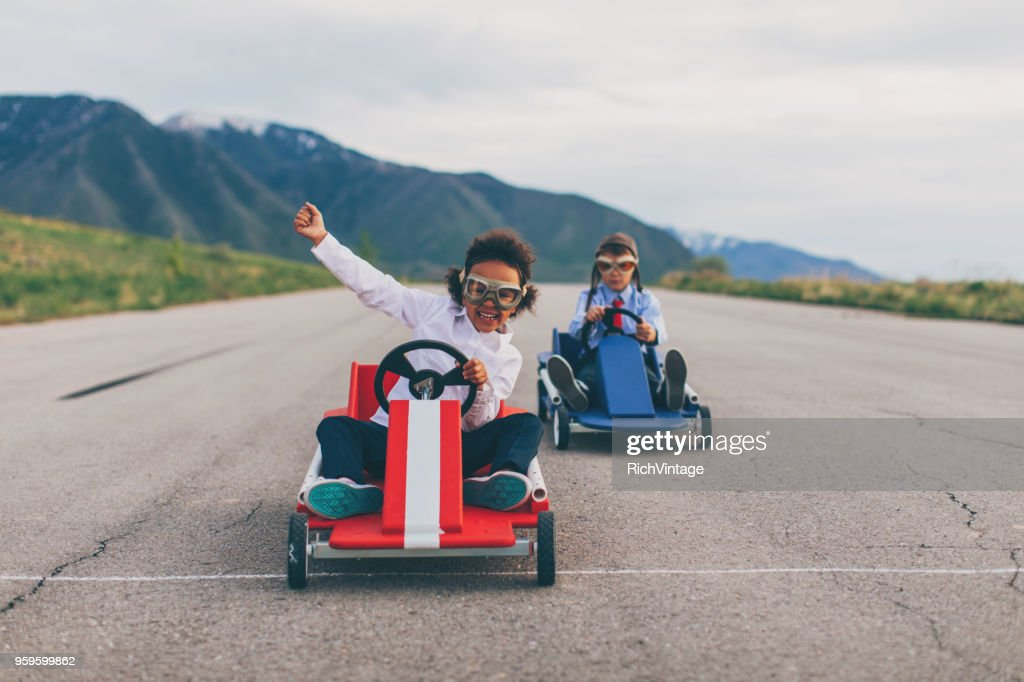 Young Business Girl Beats Boy in Car Race : Stock Photo
