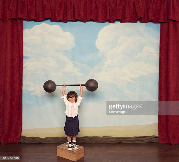 Young Business Girl Lifts Barbell on Stage