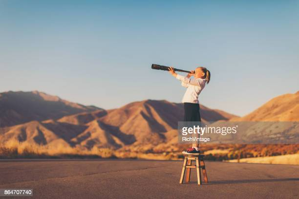 young business girl looks through telescope - dedizione foto e immagini stock