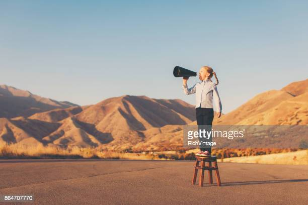 a young business girl uses megaphone - comunicazione foto e immagini stock