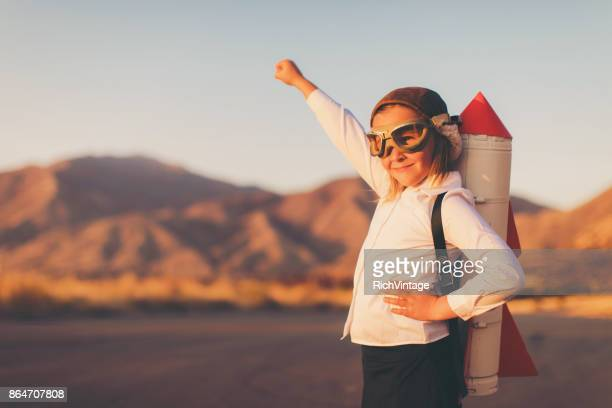 young business girl with rocket pack - dedizione foto e immagini stock