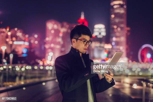 Young business man checking email on digital tablet at night