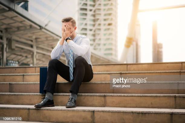 young business man crying abandoned lost in depression sitting on ground street concrete stairs suffering emotional pain, sadness, looking sick in grunge lighting - being fired stock pictures, royalty-free photos & images