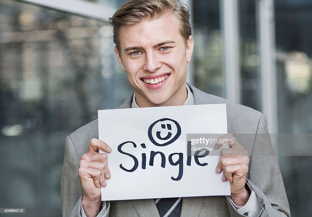"""Young business man holding """"single"""" sign : Stock Photo"""