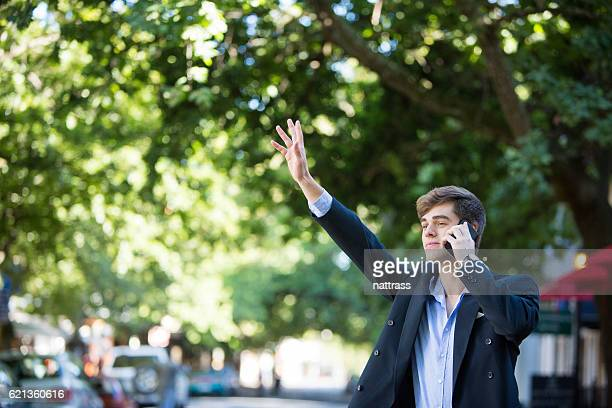 Young business man on his phone waves a taxi
