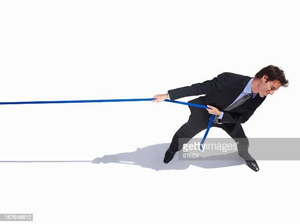 Giovane uomo d'affari tirando una corda su bianco