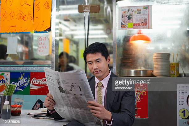 Young business man reading newspaper in fast food restaurant