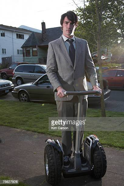 Young business man riding segway on pavement
