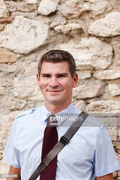 Young business man standing against brick wall