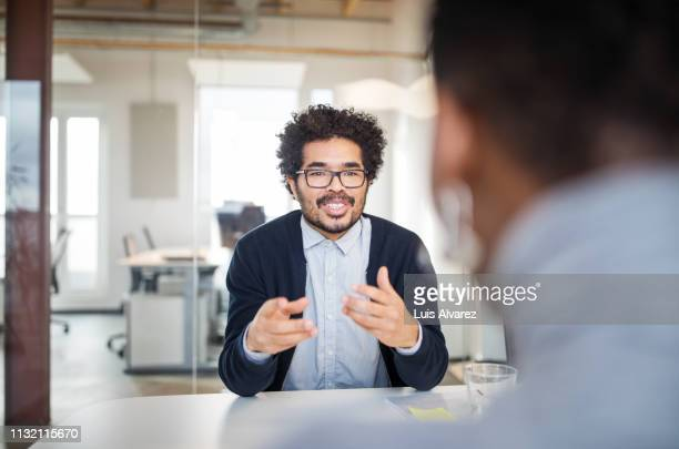 young business man talking with female colleague - explaining stock pictures, royalty-free photos & images