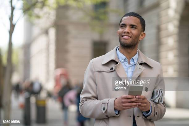 Young business man texting on the phone on the street