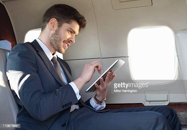young business man using graphics tablet on plane - premium access stock pictures, royalty-free photos & images