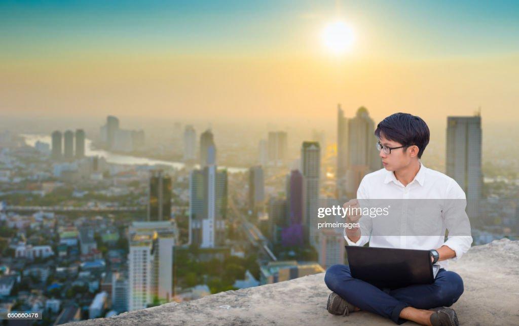 Jonge zakenman met laptop en digitale tablet stadsgezicht achtergrond : Stockfoto
