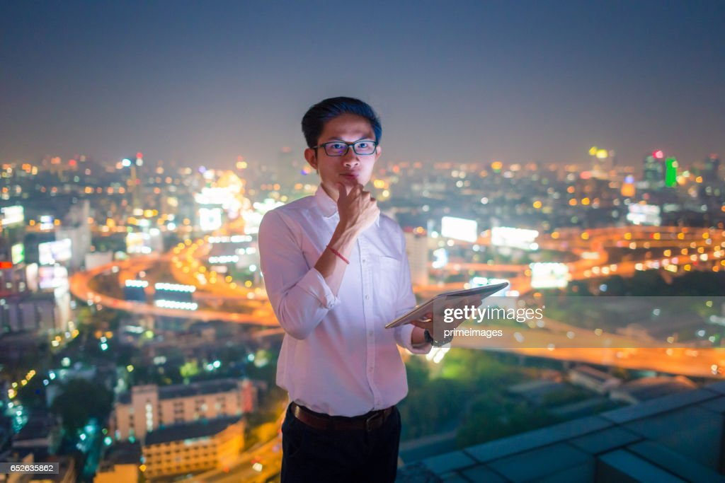 Young business man using laptop and digital tablet cityscape background : Stock Photo