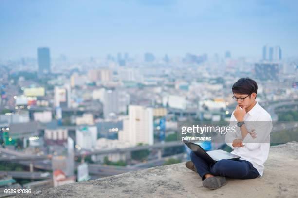 Homme d'affaires jeune en utilisant l'ordinateur portable et tablette numérique paysage urbain historique