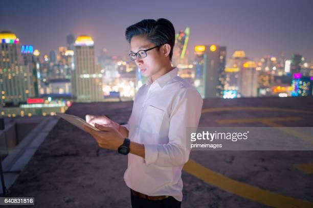 Homme d'affaires jeune à l'aide d'ordinateur portable et tablette paysage urbain