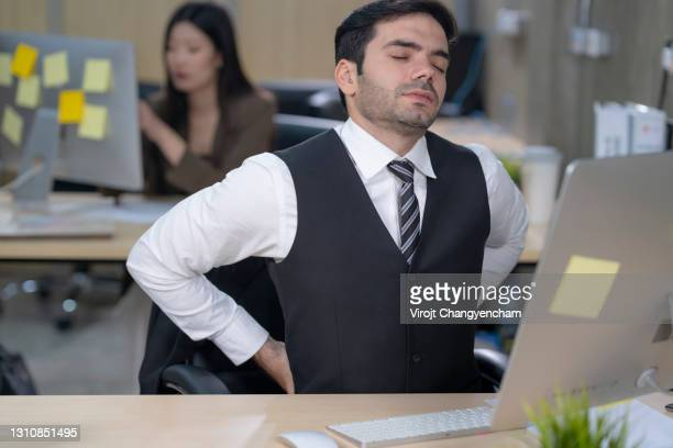 young business man waist back pain at office - 下背部 ストックフォトと画像
