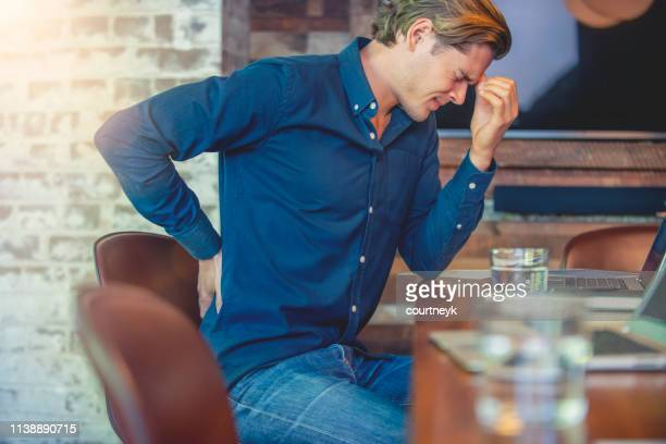 young business man with holding his back in pain. - lower back stock pictures, royalty-free photos & images