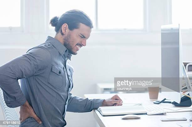Junge business Mann hält seinen Rücken Schmerzen.