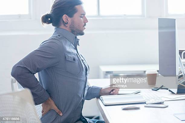 Young business man with holding his back in pain.