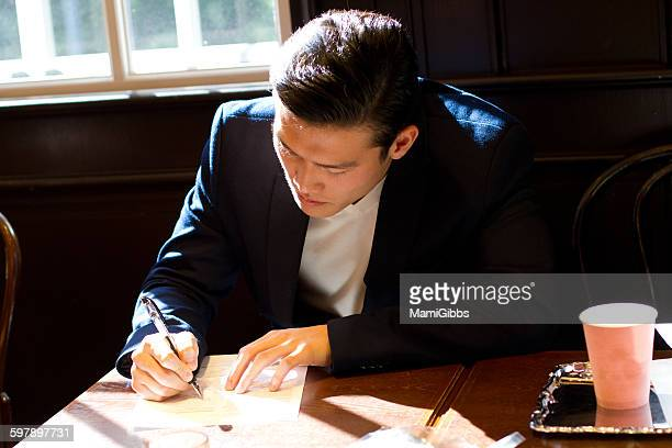 young business man writing the document - mamigibbs stock photos and pictures