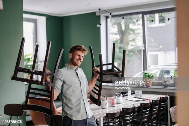 young business owner lifting chairs - leidenschaft stock-fotos und bilder