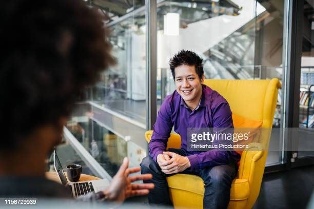 young business owner sitting in chair talking to associate - adulte d'âge moyen photos et images de collection