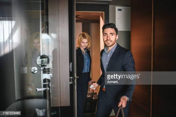jonge zaken partners die een moderne hotel kamer betreden - kantoorromance stockfoto's en -beelden