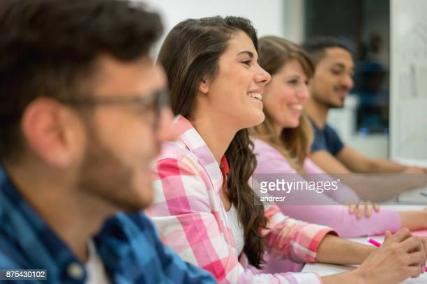 young business people at a meeting looking very happy and smiling focusing on a beautiful woman - equipamento à base de papel imagens e fotografias de stock