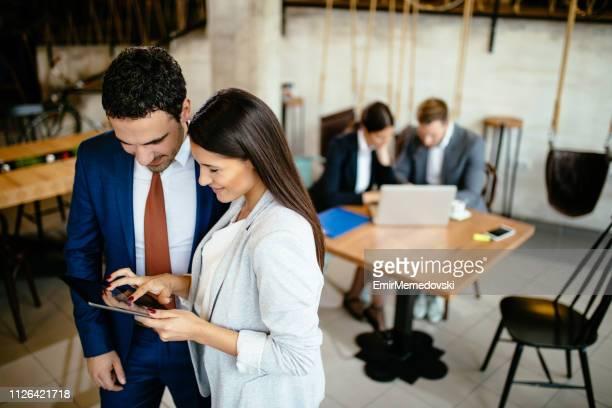 jovens empresários discutindo a estratégia de negócios usando tablet digital - figurantes incidentais - fotografias e filmes do acervo