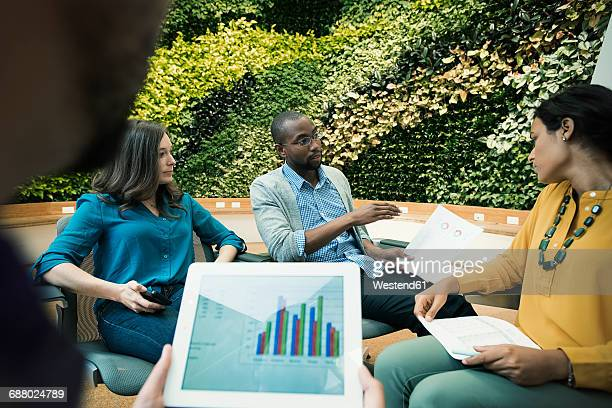 Young business people discussing in front of green plant wall