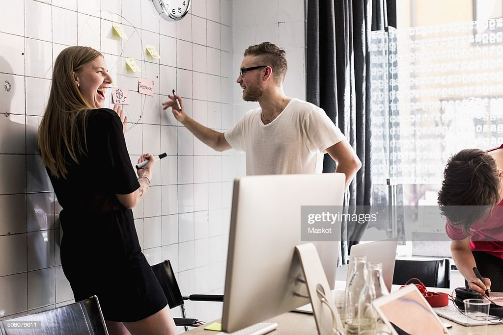 Young business people discussing on adhesive notes in new office : Stock Photo