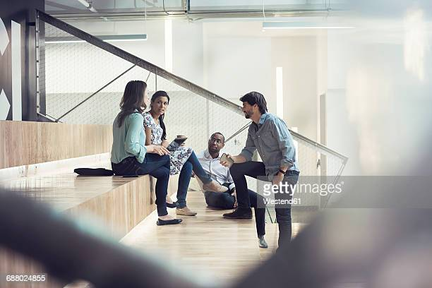 young business people discussing, sitting on stairs - businesswear stock pictures, royalty-free photos & images