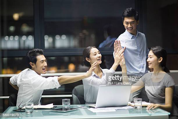 Young business people high fiving in meeting