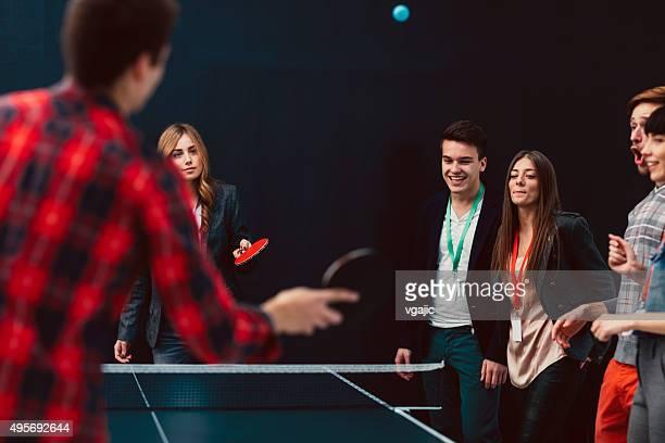 Jovens negócios pessoas a jogar ténis de mesa em seu escritório.