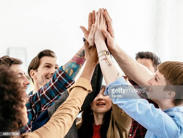 人々を示す若いビジネスチームの精神に盛り上がった腕