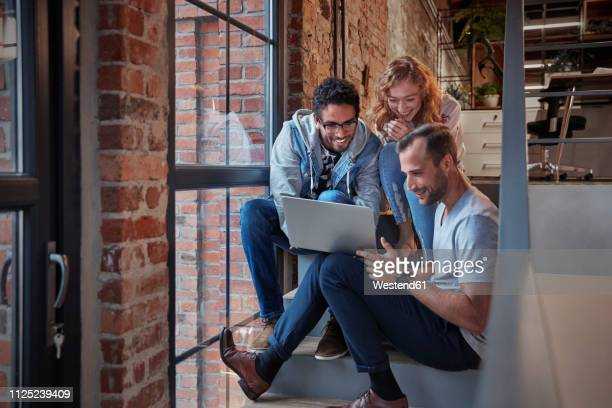 young business people sitting on stairs in loft office using laptop - three people stockfoto's en -beelden