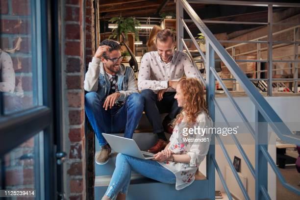 young business people sitting on stairs in loft office using laptop - zugänglichkeit stock-fotos und bilder