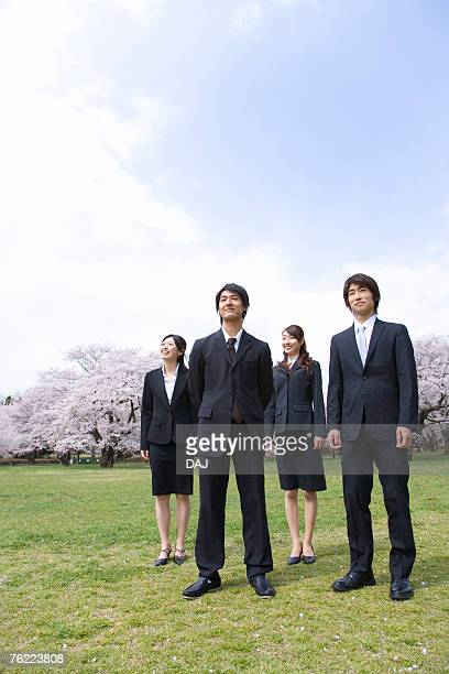 Young business people standing at the field of cherry blossoms, low angle view, front view, copy space, Japan