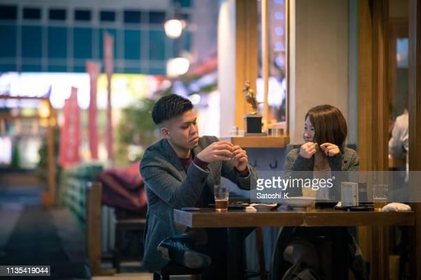 仕事の後、居酒屋で話している若いビジネスマン - evening meal ストックフォトと画像