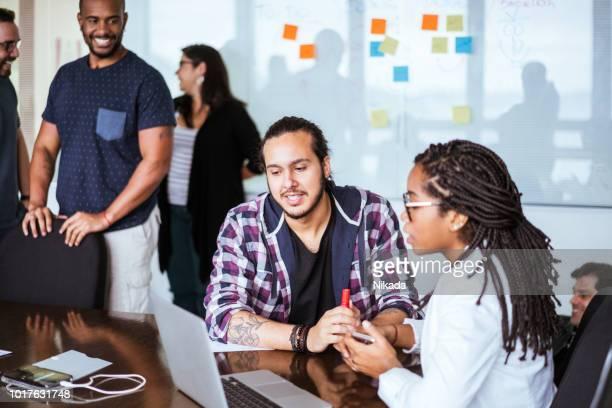 Junge Geschäftsleute mit Laptop während der Diskussion am Schreibtisch im Büro